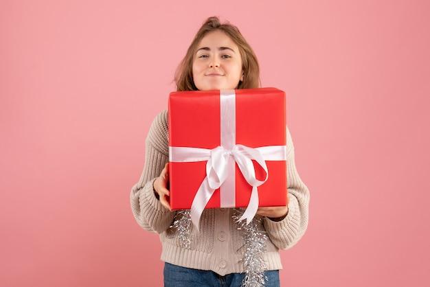 Junge frau, die weihnachten in ihren händen auf rosa hält