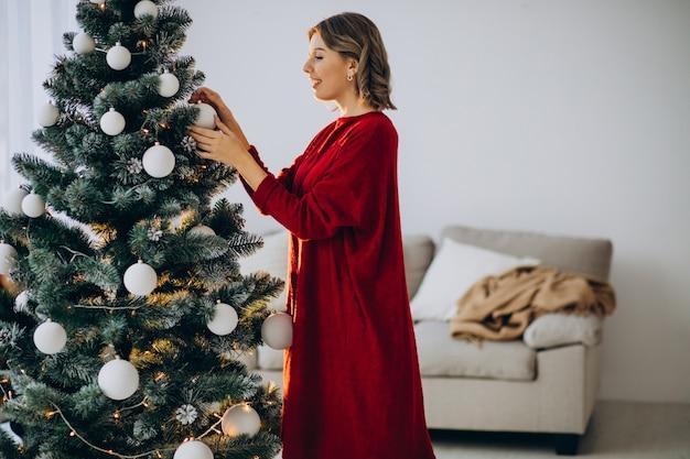 Junge frau, die weihnachtsbaum verziert