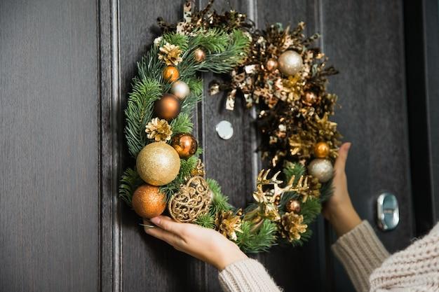 Junge frau, die weihnachtsfestkranz an der haustür hängt. traditionelle hauptdekoration an winterferien, weibliche handnahaufnahme, die handgemachten kranz des tannenbaums auf tür hält.
