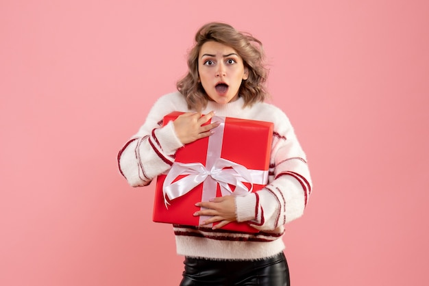 Junge frau, die weihnachtsgeschenk auf rosa hält