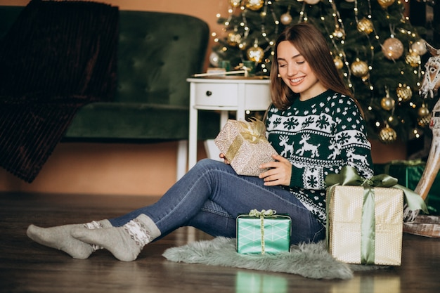 Junge frau, die weihnachtsgeschenk durch den weihnachtsbaum auspackt