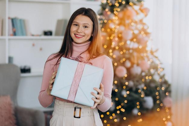 Junge frau, die weihnachtsgeschenk durch weihnachtsbaum hält