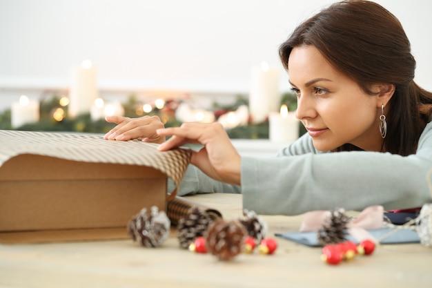 Junge frau, die weihnachtsgeschenk einwickelt