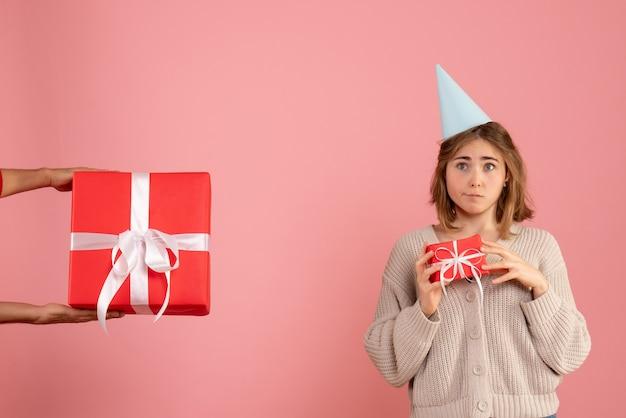 Junge frau, die weihnachtsgeschenk hält und geschenk vom mann auf rosa annimmt