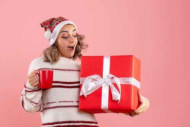 Junge frau, die weihnachtsgeschenk und tasse tee auf rosa hält