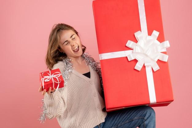 Junge frau, die weihnachtsgeschenkbox auf rosa hält