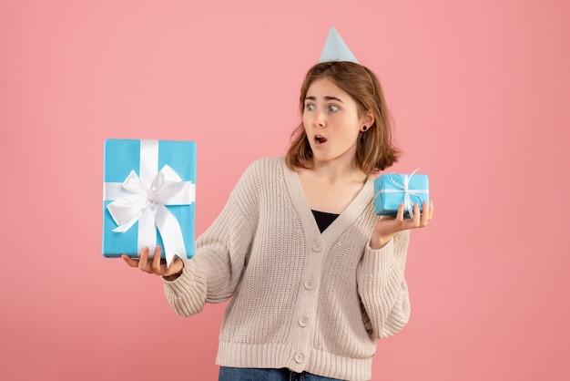 Junge frau, die weihnachtsgeschenke auf rosa hält