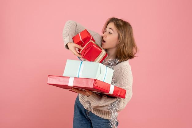 Junge frau, die weihnachtsgeschenke auf rosa trägt