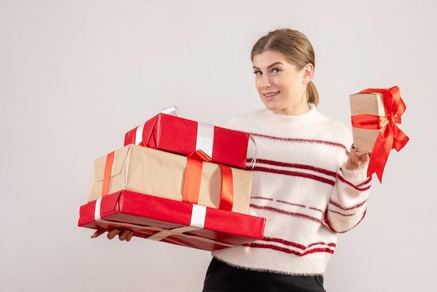 Junge frau, die weihnachtsgeschenke auf weiß trägt