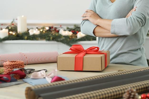 Junge frau, die weihnachtsgeschenke einwickelt