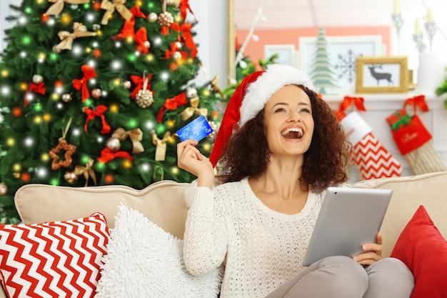 Junge frau, die weihnachtsgeschenke online bestellt
