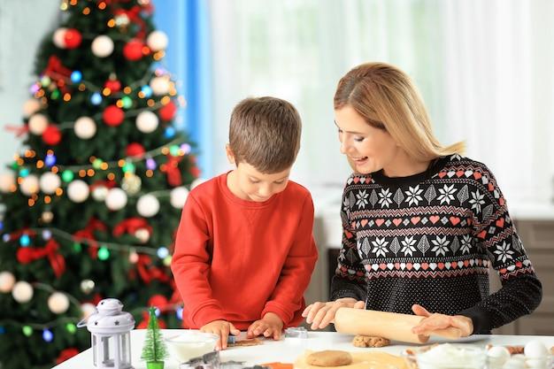 Junge frau, die weihnachtsplätzchen mit kleinem sohn in der küche zubereitet