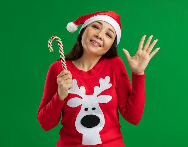 Junge frau, die weihnachtsweihnachtsmütze und roten pullover hält, der zuckerstange hält, die kamera glücklich und fröhlich winkend mit hand steht über grünem hintergrund betrachtet