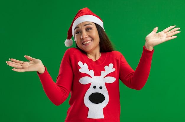 Junge frau, die weihnachtsweihnachtsmütze und roten pullover trägt, der lächelnde kamera betrachtet, verwirrt verwirrt achselzucken über grünem hintergrund steht