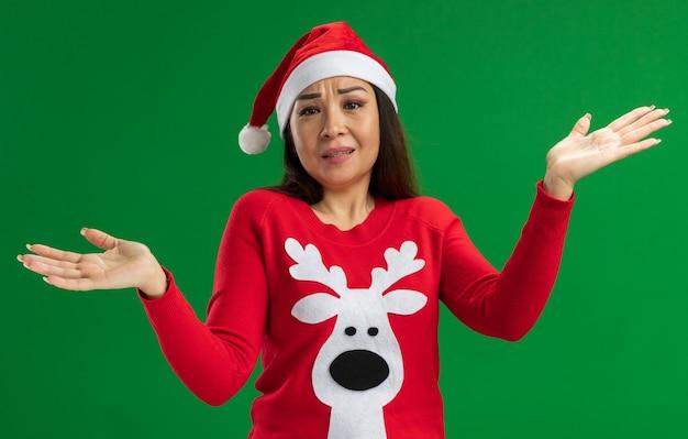 Junge frau, die weihnachtsweihnachtsmütze und roten pullover trägt, der verwirrte achselzucken steht, die über grünem hintergrund stehen