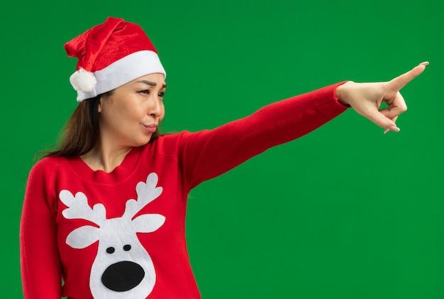 Junge frau, die weihnachtsweihnachtsmütze und roten pullover trägt, die beiseite schauen mit ernstem gesicht, das mit zeigefinger zeigt, der über grünem hintergrund steht