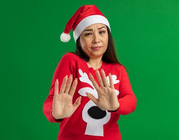 Junge frau, die weihnachtsweihnachtsmütze und roten pullover trägt, die kamera besorgt betrachten, macht verteidigungsgeste, die hände heraussteht, die über grünem hintergrund stehen