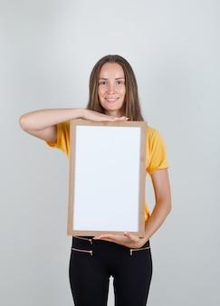 Junge frau, die weiße tafel hält und im gelben t-shirt lächelt