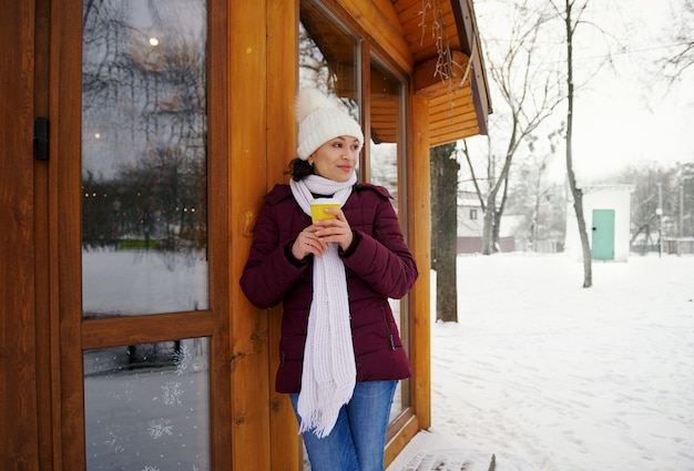 Junge frau, die weiße wollstrickmütze und schal trägt, die heißes getränk während des frostigen kalten tages im park genießen.