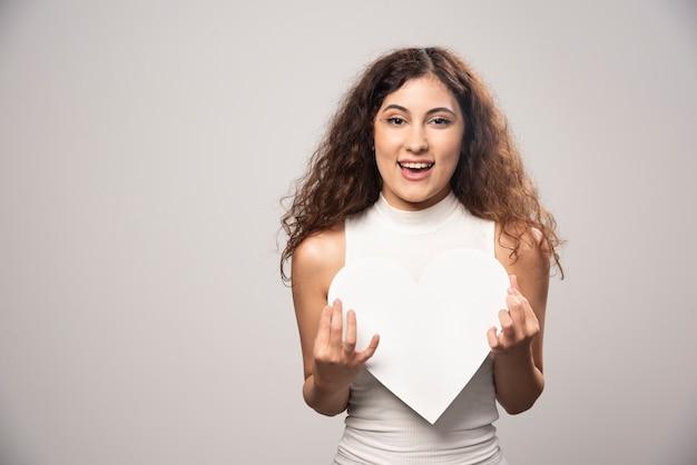 Junge frau, die weißes handgemachtes papierherz hält. hochwertiges foto