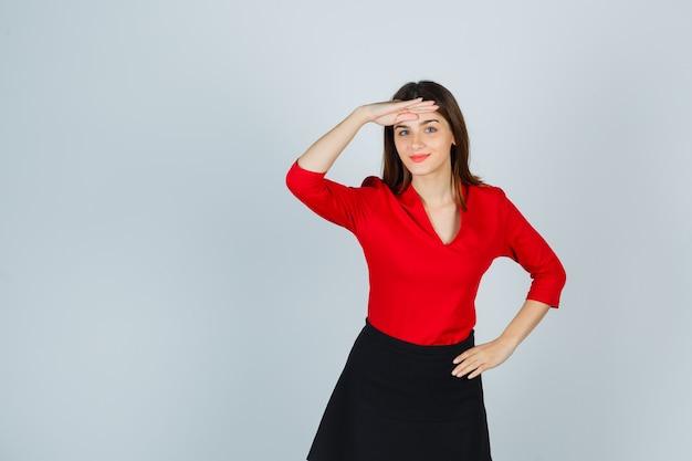 Junge frau, die weit weg mit hand über kopf schaut und hand auf hüfte in roter bluse hält