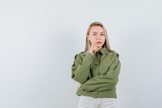 Junge frau, die wie das fokussieren auf etwas in der grünen jacke aufwirft und schöne vorderansicht sieht.