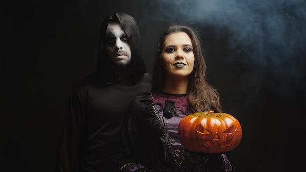 Junge frau, die wie eine hexe verkleidet ist und eine jack o lantern für halloween neben einem dunklen sensenmann auf schwarzem hintergrund hält