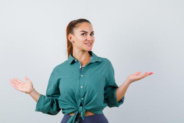 Junge frau, die willkommensgeste im grünen hemd zeigt und fröhlich aussieht, vorderansicht.