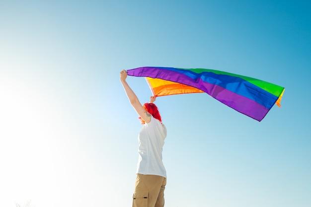 Junge frau, die winkende lgbt-flagge über kopf hält