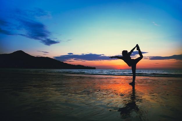 Junge frau, die yoga auf dem beah tut
