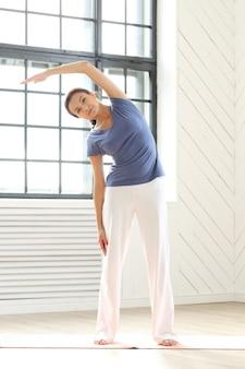 Junge frau, die yoga auf einer yogamatte praktiziert