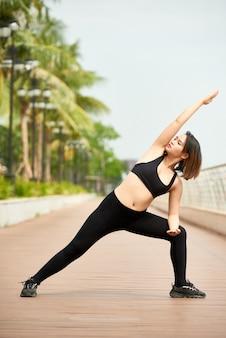 Junge frau, die yoga auf seeseite tut