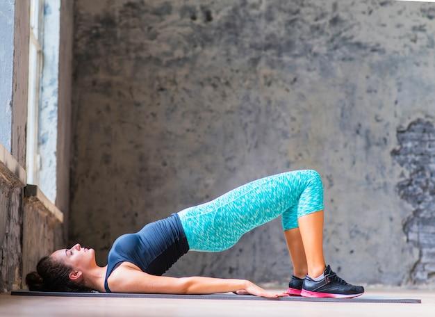Junge frau, die yoga auf übungsmatte tut