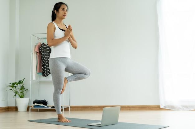 Junge frau, die yoga-baum-haltung zu hause tut. betrachten des laptop-bildschirms, gesundes lebensstilkonzept