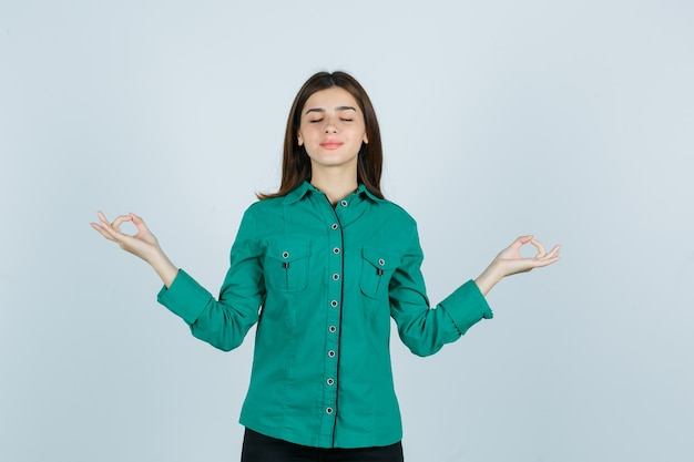 Junge frau, die yoga-geste mit geschlossenen augen im grünen hemd zeigt und entspannt, vorderansicht schaut.