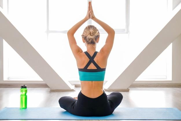 Junge frau, die yoga im fitnessstudio praktiziert