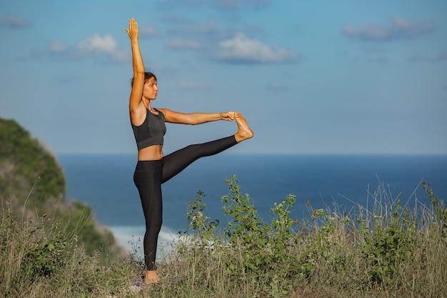 Junge frau, die yoga im freien mit erstaunlicher rückansicht tut. bali. indonesien.