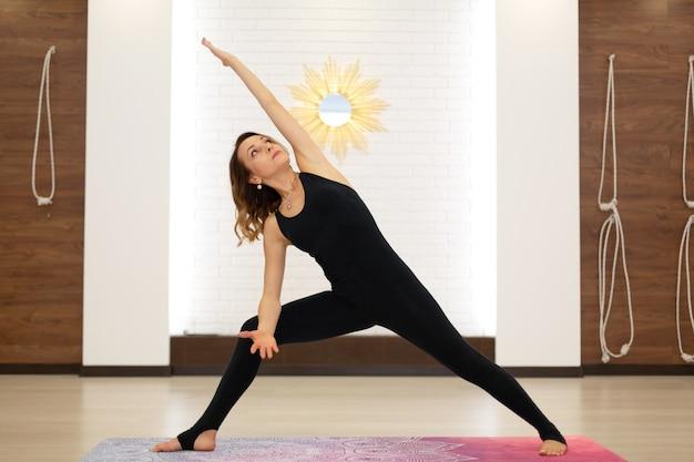 Junge frau, die yoga im hellen fitnessstudio praktiziert. stretching und wellness-lifestyle.