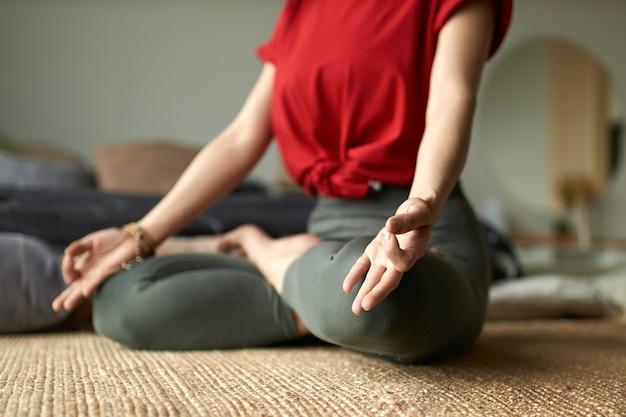 Junge frau, die yoga im lotussitz zu hause tut