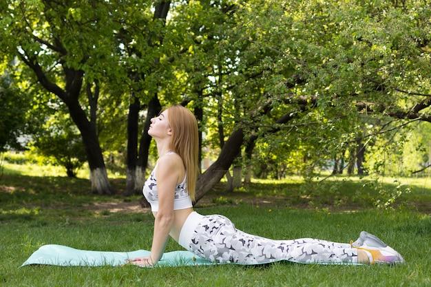 Junge frau, die yoga im park tut