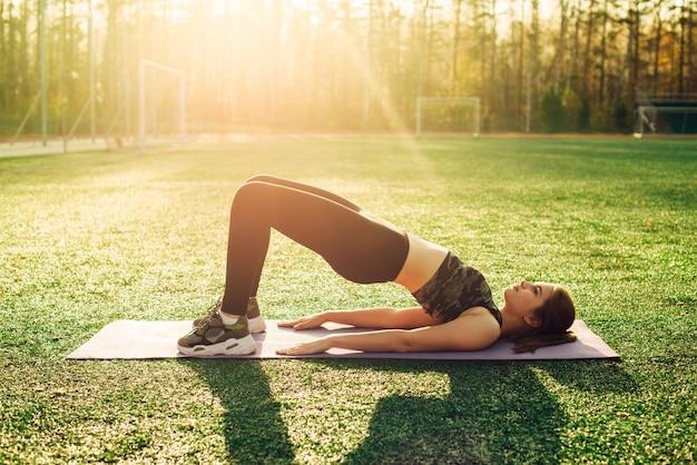 Junge frau, die yoga im stadion tut