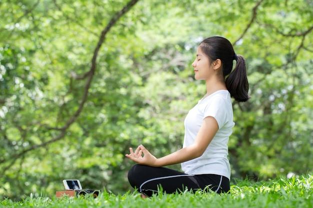 Junge frau, die yoga in der natur praktiziert, asiatische frau praktiziert yoga im stadtpark