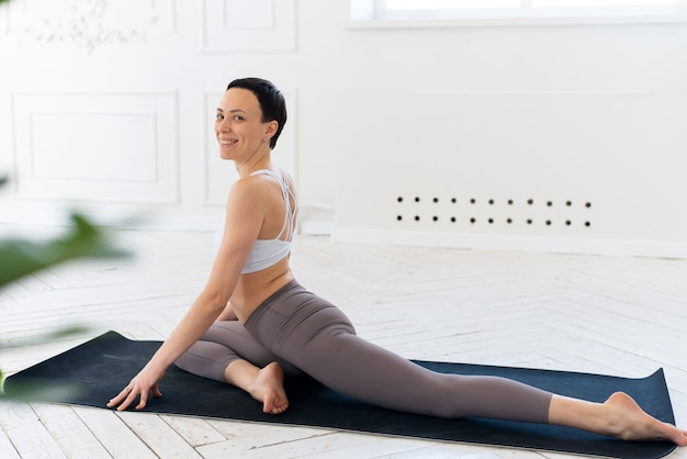 Junge frau, die yoga in einem hellen hintergrund praktiziert. gesundes lebensstilkonzept.