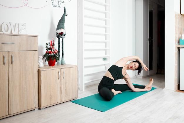 Junge frau, die yoga in ihrer eigenen wohnung ausübt und ihren tag genießt