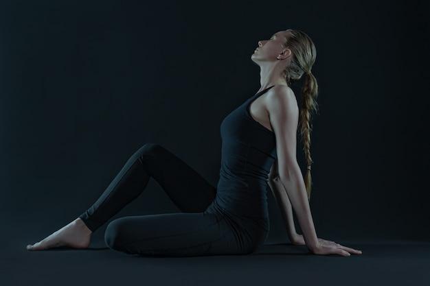 Junge frau, die yoga-position praktiziert. yoga-matte und leggins auf einem dunklen schwarzen hintergrund. speicherplatz kopieren.