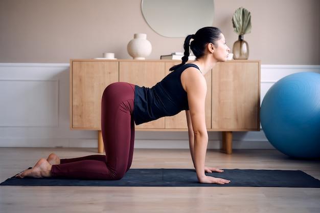 Junge frau, die yoga praktiziert und in der nach unten gerichteten hundehaltung steht