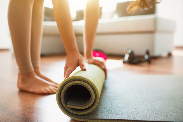 Junge frau, die yoga-training im raum tut. schneiden sie niedrige ansicht des barfußmädchens, das yogamatte aufrollt, nachdem sie dehnung oder übung beendet haben.