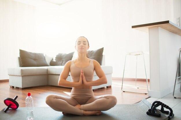 Junge frau, die yoga-training im raum während der quarantäne tut. setzen sie sich mit gekreuzten beinen und händen zusammen in die spielposition. meditieren auf der matte im zimmer. ruhiges friedliches mädchen, das trainiert.