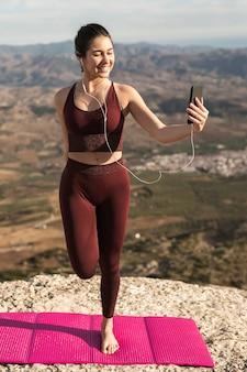 Junge frau, die yoga tut und telefon verwendet