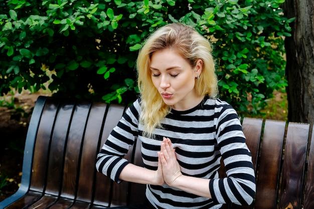 Junge frau, die yoga-übung und meditation tut, die auf einer bank in einem park in gestreifter spitze sitzen